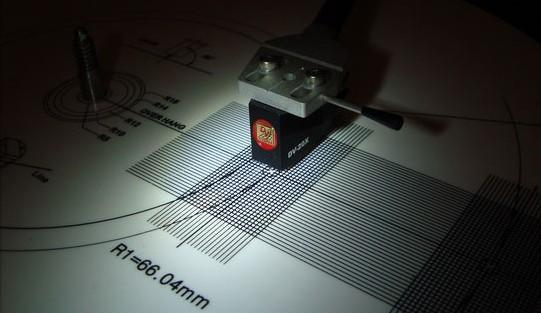Papírové pravítko-šablona pro nastavení vzdálenosti přenosky od osy otáčení raménka.