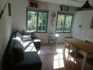 Kuchyně a výhled na zahradu a vodu Jesenické přehrady. Gauč lze rozložit (lze i přespat na gauči). Chata k pronájmu u přehrady Jesenice