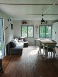 Pokoj chaty u Jesenice stůl, židle, gauč - rozkládací (lze i přespat). Výhled na vodu - přehradu a zahradu.