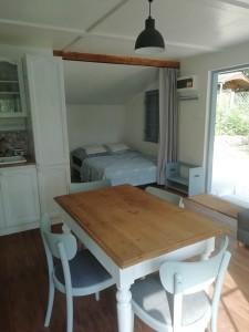 Kuchyň, kuchyňská linka, boiler ve skříni, stůl, židle, postel pro dvě osoby za závěsem. Chata k pronájmu u vody - Jesenická přehrada, koupání.